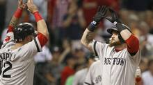 Boston Red Sox's Mike Napoli (12) welcomes Jonny Gomes home after he hit a three-run home run against the Houston Astros in the sixth inning of a baseball game Tuesday, Aug. 6, 2013, in Houston. (Pat Sullivan/AP)