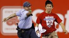 A law enforcement officer prepares to taser a fan that ran onto the field before the eighth inning of a baseball game between the Philadelphia Phillies and the St. Louis Cardinals, Monday, May 3, 2010, in Philadelphia. St. Louis won 6-3. (Matt Slocum/AP)