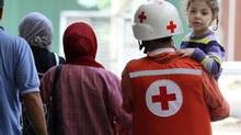 A Red Cross rescue member helps a family cross a street at the Bab al-Tebbaneh neighbourhood in Tripoli, northern Lebanon, May 14, 2012. A $34.7-million Red Cross text campaign to aid victims of the 2010 Haiti earthquake was put together by a team of women that included a special adviser at the State Department, leaders at the Red Cross, and Jenifer Snyder, a lawyer who created the platform with women technologists. (STRINGER/REUTERS)