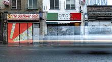 Traffic passes the painted shutters of closed shops in Shoreditch, in London (LUKE MACGREGOR/REUTERS)