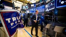 A trader walks past a campaign sign for U.S. President-elect Donald Trump and U.S. Vice President-elect Mike Pence on the floor of the New York Stock Exchange (NYSE) in New York, U.S., on Wednesday, Nov. 9. (Michael Nagle/Bloomberg)