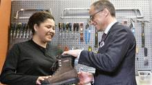 Alberta Finance Minister Joe Ceci donates work boots to Women Building Futures student Kim Brertton during a pre-budget photo opportunity in Edmonton. (JASON FRANSON/THE CANADIAN PRESS)