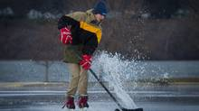 Aidan Chassie, 15, attempts to stick handle through a puddle on the rink at Pier 8 on Hamilton's Waterfront on Christmas afternoon while playing keep-away with his dad Rick