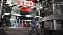 People walk past the TED logo at the Vancouver Convention Centre where the TED conference will take place March 17-21. (Rafal Gerszak For The Globe and Mail)