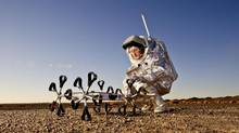 A scientist wears an Aouda Mars space suit simulator as he stands next to the Hungarian Google Lunar X-Prize Rover Puli in the desert of Morocco in February, 2013. Between Feb. 1 and 28, the Austrian Space Forum – in partnership with the Ibn Battuta Center in Marrakesh – conducted an integrated Mars analog field simulation in the northern Sahara near Erfoud in Morocco. (HANDOUT/REUTERS)