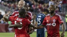 Toronto FC's Jermain Defoe (centre left) celebrates with (left to right) Michael Bradley, Jackson Goncalves and Collen Warner after he scores from the penalty spot to level against Vancouver Whitecaps during second half MLS action in Toronto on Wednesday July 16, 2014. (The Canadian Press)