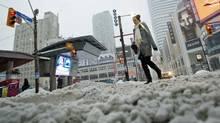 A pedestrian makes her way through the snow and slush in downtown Toronto, Feb, 2, 2011. (Darren Calabrese / CP/Darren Calabrese / CP)