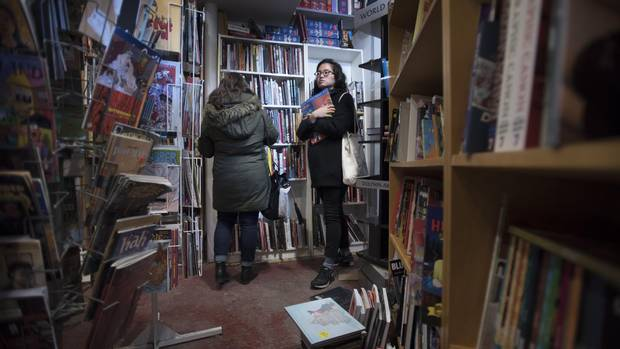 Nicole Kim (right) and her friend Lisa Benedetto browse the shelves for books while shopping at The Beguiling.