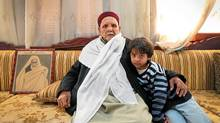 Mohammed Omar Al-Mukhtar, 90, leader of the Imnifa tribe at home in Benghazi with 6-year old Mohammed Yousif, a relative. On the couch beside him sits a photograph of his late father, also named Omar Al-Mukhtar, a famous hero of the resistent against Italian occupation. (Charla Jones/Charla Jones for The Globe and Mail)