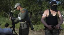 Armed Pro-Russian men prepare themselves to confront Ukrainian government troops at a checkpoint outside Slovyansk, eastern Ukraine, Thursday, May 15, 2014. (AP Photo/Alexander Zemlianichenko) (Alexander Zemlianichenko/AP)