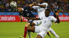 France's Karim Benzema fights for the ball with Osman Chavez and Maynor Figueroa of Honduras during their 2014 World Cup Group E soccer match in Porto Alegre, June 15, 2014. (DAMIR SAGOLJ/REUTERS)
