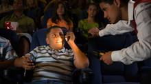 Kid busted for using cellphone in movie theatre. (Thinkstock)