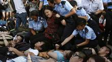 A protester reacts as she is dragged away by policewomen on a street outside HSBC headquarters at Hong Kong's financial Central district July 2, 2014, after staying an overnight sit-in with fellow demonstrators. (BOBBY YIP/REUTERS)