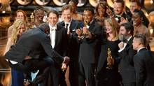 "Director Steve McQueen, left, celebrates with the cast and crew of ""12 Years a Slave"" as they accept the award for best picture during the Oscars at the Dolby Theatre on Sunday, March 2, 2014, in Los Angeles. (John Shearer/Invision/AP)"