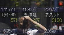 A man is reflected on an electronic monitor displaying share prices outside a brokerage in Tokyo, July 9, 2012. (ISSEI KATO/REUTERS)