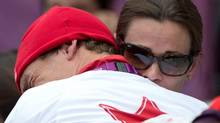 Canada's Simon Whitfield is hugged by his wife after crashing and retreating from the men's triathlon at Hyde Park during the Summer Olympics in London on Tuesday, August 7, 2012. (Sean Kilpatrick/THE CANADIAN PRESS)