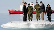 Prime Minister Stephen Harper, second from right, stands on an iceberg as he talks with Chief of the Defence Staff General Walter Natynczyk (centre) as they take part in a training exercise during Operation Nanook in Resolute, Nunavut on the third day of his five-day northern tour to Canada's Arctic on Wednesday Aug. 25, 2010. The Canadian Coast Guard's medium icebreaker Henry Larsen is seen in Allen Bay. (Sean Kilpatrick/The Canadian Press)