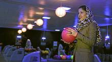 Meena Rahmani, 26, owner of The Strikers, the country's first bowling center, holds a bowling ball in Kabul, Afghanistan. In an Afghan capital scarred by years of war, a young Afghan woman has bet $1 million that the country could use a chance to have a bit of fun _ by bowling. Located just down the street from Kabul's glitziest mall, Meena Rahmani opened Afghanistan's first bowling alley, offering a place where Afghan men, women and families can gather, relax, bowl a few games and not be burdened by the social, religious and cultural restrictions that govern daily life in the impoverished country. (Muhammed Muheisen/The Associated Press/Muhammed Muheisen/The Associated Press)