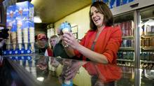 Wildrose Leader Danielle Smith serves ice cream at a campaign stop in Strathmore, Alta., on Saturday. (Jeff McIntosh/The Canadian Press)