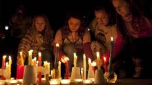Young people place candles during a memorial for Amanda Todd in Surrey, B.C. (JONATHAN HAYWARD/THE CANADIAN PRESS)