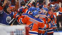 Oilers teammates celebrate their Game 5 overtime win over the Sharks. (Jeff McIntosh/THE CANADIAN PRESS)