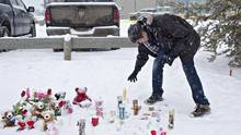 A resident of La Loche, Sask., pays his respects on Jan. 23, 2016, to the victims of a school shooting. (JASON FRANSON/THE CANADIAN PRESS)