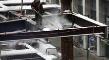 A construction worker sweeps snow from iron beams on the Bay Adelaide East office building site in Toronto on Feb. 6, 2014. (CHRIS HELGREN/REUTERS)