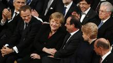 German Chancellor Angela Merkel, third left, and French President François Hollande, third right, touch hands during the Nobel Peace Prize ceremony at City Hall in Oslo, Dec. 10, 2012. (SUZANNE PLUNKETT/REUTERS)