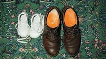 Baby sneakers on the carpeted floor next to a pair of man's dress shoes. (Thinkstock/Getty Images)