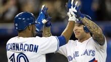 Toronto Blue Jays Edwin Encarnacion and Brett Lawrie celebrate after scoring during the sixth inning Tuesday. (Frank Gunn/The Canadian Press/Frank Gunn/The Canadian Press)