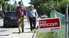 Aid Adam De Claire, left, and Liberal candidate Peter Milczyn, knock on doors in Etobicoke, Ontario Thursday, July 25, 2013. (Kevin Van Paassen/The Globe and Mail)