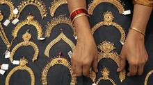 A woman checks a gold necklace inside a jewellery showroom in the southern Indian city of Hyderabad April 11, 2012. Indian gold futures are likely to extend losses this week, falling below a one-week low touched on Monday, hurt by a firm dollar overseas, although a revival in physical demand ahead of key festival could limit the downside, analysts said. Picture taken April 11, 2012. (Krishnendu Halder/Reuters)