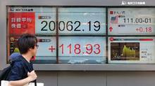 A pedestrian walks past a stock quotation board flashing the key Nikkei index of the Tokyo Stock Exchange in front of a securities company in Tokyo on June 19, 2017. (KAZUHIRO NOGI/AFP/Getty Images)