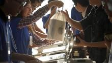 In this Nov. 2, 2012, file photo, a staff member at a Hong Kong Apple store serves a customer. (Vincent Yu/AP)