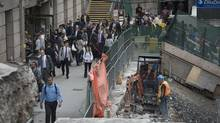Pedestrians make their way past a construction site in front of Union Station in Toronto. City staff are throwing cold water on a proposal to rename the station for Sir John A. Macdonald. (Darren Calabrese For The Globe and Mail)
