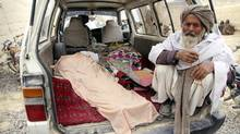 An elderly Afghan man sits next to the covered body of a person who was allegedly killed by a U.S. service member in Panjwai, Kandahar province south of Kabul, Afghanistan, Sunday, March 11, 2012. (Allauddin Khan/AP/Allauddin Khan/AP)