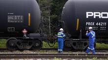 Inspectors for the transportation of dangerous goods (TDG) inspect a train on the track approximately 10km (6 miles) outside of the site of a derailment in Lac Megantic, Quebec, July 7, 2013. A driverless freight train carrying tankers of petroleum products derailed at high speed and exploded into a giant fireball in the middle of the small Canadian town of Lac-Megantic early on Saturday, destroying dozens of buildings and leaving an unknown number of people feared missing. (CHRISTINNE MUSCHI/REUTERS)