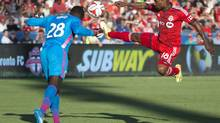 Toronto FC forward Jermain Defoe (18) battles for a ball with D.C. United goalkeeper Bill Hamid (28) during the first half in a game at BMO Field on July 5, 2014. (Nick Turchiaro/USA Today Sports)