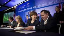 B.C. Premier Christy Clark, left, and Roy Morris, Nee Tahi Buhn Indian Band Chief, add their signatures to a Benefit Agreement at the International LNG Conference in Vancouver on Feb. 25, 2013. (Rafal Gerszak for The Globe and Mail)