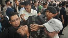 This file photo taken on November 25, 2011 shows security personnel evacuating a man after he collapsed while queueing for discounted BlackBerry smart phones at a mall in Jakarta. (DANNY/DANNY/AFP/Getty Images)