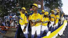 Members of the Jackie Robinson West Little League team from Chicago, Ill., ride in the Little League Grand Slam Parade (Gene J. Puskar/AP)