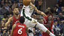 Milwaukee Bucks' Giannis Antetokounmpo passes the ball out after being stopped by Toronto Raptors' Jonas Valanciunas, left, DeMarre Carroll, right, and Cory Joseph, centre, during the first half of an NBA basketball game Saturday, March 4, 2017, in Milwaukee. (Tom Lynn/The Associated Press)
