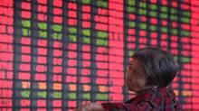 An investor reacts in front of an electronic board showing stock information at a brokerage house in Taiyuan, Shanxi province July 3, 2012. China's main stock index closed largely flat on Tuesday, finishing up 0.1 percent. (REUTERS)