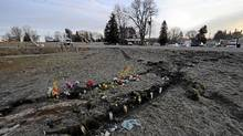 Flowers and candles, placed in the trough left behind by truck tires at the scene of a fatal vehicle accident in Hampstead, Ont., is photographed Feb. 8, 2012. (Fred Lum/The Globe and Mail/Fred Lum/The Globe and Mail)