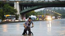 A man rides his bicycle through a flood on the Don Valley Parkway, a major highway in Toronto, during a heavy rainstorm July 8. (Mark Blinch/REUTERS)