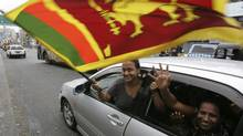 Sri Lankans wave their national flag as they celebrate the military victory over Tamil Tiger rebels in Colombo on May 20, 2009. (Eranga Jayawardena/Associated Press)