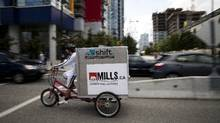 Graham Anderson, an employee at Shift Urban Cargo Delivery, rides a cargo bicycle to pick up packages to deliver in downtown Vancouver, Aug. 8, 2011. (Rafal Gerszak for The Globe and Mail/Rafal Gerszak for The Globe and Mail)