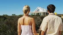 Young couple looking at summer home (Stockbyte/Photos.com)