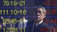A man is reflected on an electronic board displaying exchange rates outside a brokerage in Tokyo on Oct. 31, 2011. Japan intervened to weaken the yen after the currency hit a record high against the dollar on Monday. (ISSEI KATO/ISSEI KATO/REUTERS)