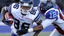Toronto Argonauts' Trent Guy (left) evades a tackle by Montreal Alouettes' Tanner Marsh after intercepting a pass during the second quarter of their CFL game Thursday June 20, 2013 in Toronto. (Jon Blacker/THE CANADIAN PRESS)